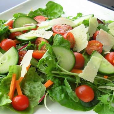 Lettuce and tomato salad with yellow cheese